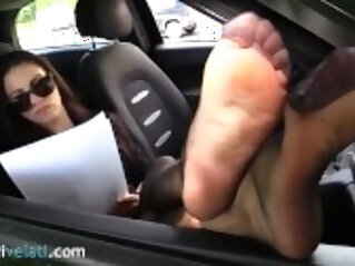 Brunette in black pantyhose shows feet from her on the road